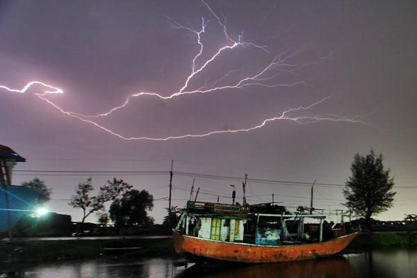 Hujan lebat disertai petir melanda kawasan kampung nelayan Karangsong, Indramayu, Jawa Barat, Kamis (27/12/2018). - ANTARA/Dedhez Anggara