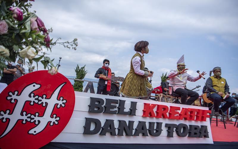 Menteri Pariwisata dan Ekonomi Kreatif (Kemenparekraf) Sandiaga Uno (tengah) didampingi Bupati Kabupaten Dairi Eddy Keleng Ate Berutu (kanan) dan istri Romy Frida Mariani Simarmata (kedua kiri) menyapa warga usai peluncuran Gerakan Nasional (Gernas) Bangga Buatan Indonesia (BBI) Beli Kreatif Danau Toba, di Paropo, Dairi, Sumatera Utara, Sabtu (20/2/2021). - Antara
