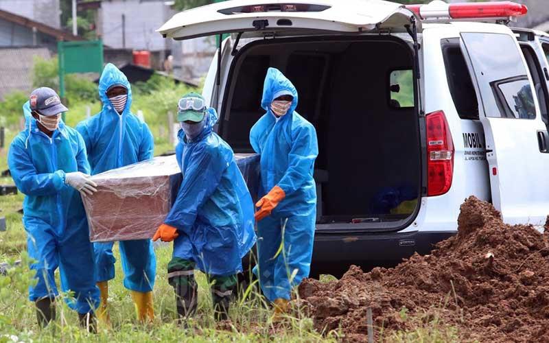 Petugas pemakaman membawa peti jenazah pasien COVID-19 di TPU Tegal Alur, Jakarta, Kamis (9/4/2020). Bisnis - Eusebio Chrysnamurti\n