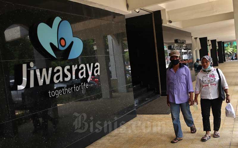 Ilustrasi - Warga melintasi logo Asuransi Jiwasraya di Jakarta, Senin (5/10/2020). Bisnis - Eusebio Chrysnamurti