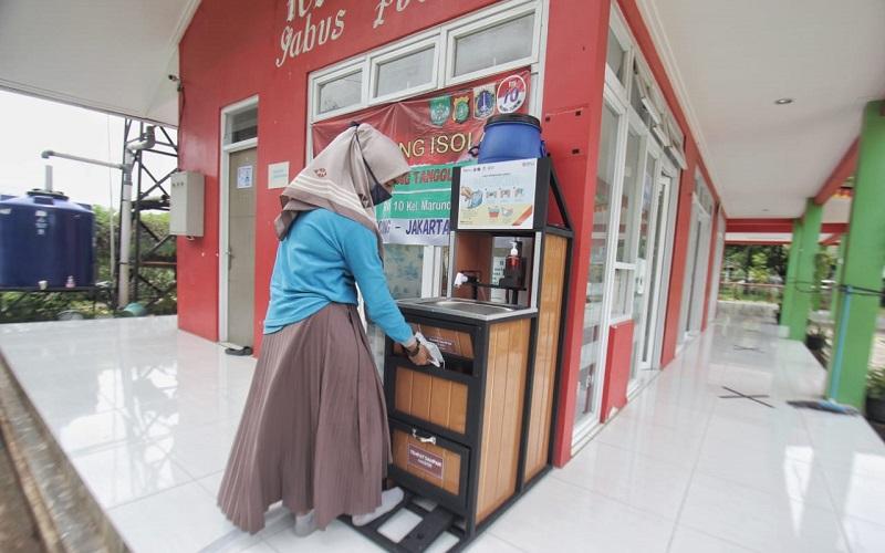 Warga sedang membuang sampah masker di tempat sampah khusus di Jakarta, Minggu (21/2/2021). BNI dan Satgas Covid-19 bekerja sama untuk mensosialisasikan cara membuang sampah masker yang benar untuk mencegah penularan virus Corona melalui limbah medis.  - dok. BNI