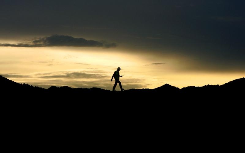 Seorang pekerja berjalan di atas tumpukan batu bara di Indonesia./Bloomberg - Dadang Tri