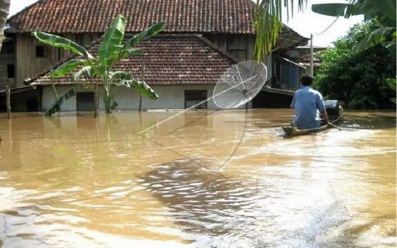 Seorang warga mengunakan perahu sebagai alat transportasi di Desa Pulau Panggung, Kecamatan Muara Kelingi, Kabupaten Musi Rawas, Sumatra Selatan, yang terendam banjir sejak, Sabtu (20/2/2021). - Antara\r\n