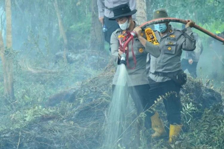 Kapolres Inhil, AKBP Dian Setyawan saat melakukan pemadaman api di Dusun Sekawan, Kecamatan Tempuling, Inhil, Minggu (21/2/2021). (ANTARA - HO/Polres Inhil)