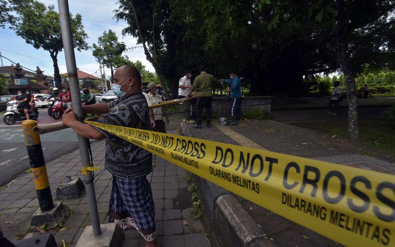 Petugas memperbaiki garis larangan memasuki area ruang publik yang dirusak warga di Lapangan Puputan Margarana Renon, Denpasar, Bali, Kamis (18/2/2021). Kegiatan tersebut untuk mencegah terjadinya kerumunan di area ruang publik pada masa Pemberlakuan Pembatasan Kegiatan Masyarakat (PPKM) skala mikro menyusul kasus Covid-19 di Bali masih fluktuatif. - Antara/Nyoman Hendra Wibowo.