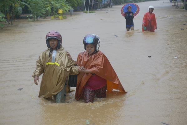 Warga menyeberangi banjir bandang yang memutus jalur lintas selatan Desa Hadiwarno, Pacitan, Jawa Timur, Selasa (28/11). Badai Siklon Tropik yang melanda kawasan pesisir selatan Jawa telah memicu hujan deras sejak sehari sebelumnya sehingga menyebabkan puluhan desa di empat kecamatan daerah itu terendam banjir bandang dan longsor. ANTARA FOTO - Destyan Sujarwoko