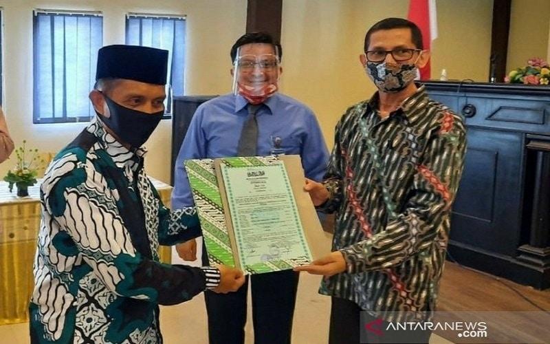 Kepala Kantor Perwakilan BI Sulteng M. Abdul Majid Ikram (tengah) menyaksikan penyerahan sertifikasi halal dari perwakilan MUI Sulteng kepada Pimpinan Pondok Pesantren Madinatul Ilmi Dolo Kabupaten Sigi Dr. Habib Ali Bin Hasan Aljufri (kanan) di Kantor Wilayah Kemenag Sulteng di Kota Palu, Kamis (20/8/2020) -