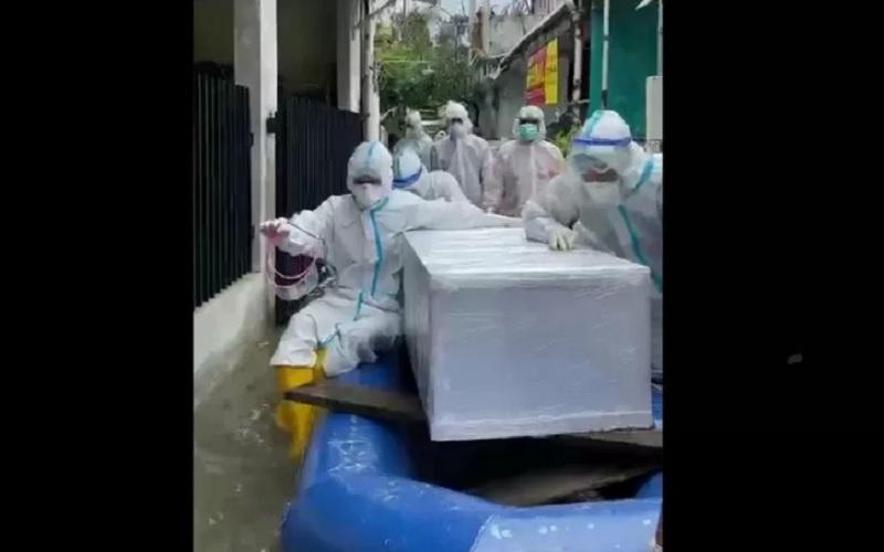 Tim Khusus Pemulsaran Jenazah Covid-19 dari Direktorat Samapta Polda Metro Jaya mengevakuasi jenazah pasien Covid-19 yang terjebak banjir di Jakarta Timur. - Antara\r\n\r\n