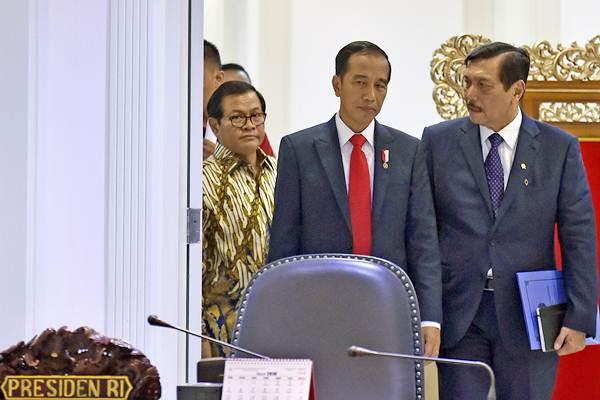 Presiden Joko Widodo (tengah) berbincang dengan Menko Kemaritiman Luhut Panjaitan (kanan) dan Seskab Pramono Anung sebelum memimpin rapat terbatas tentang insentif investasi di Kantor Presiden, Jakarta, Selasa (20/2/2018). - ANTARA/Puspa Perwitasari