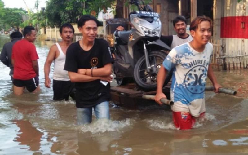 Warga mengangkut sepeda motor di tengah banjir. - Antara/Pradita Kurniawan Syah