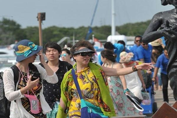 Sejumlah wisatawan melihat patung nelayan setibanya mereka dari berwisata dengan kapal laut di dermaga Serangan, Denpasar.  - Antara