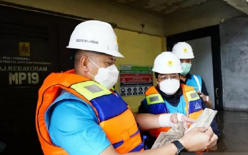 Petugas PLN meninjau lokasi terdampak banjir di wilayah DKI Jakarta, Sabtu (20/2/2021). PLN terus siaga untuk penanganan dan pengamanan kelistrikan.  - Antara
