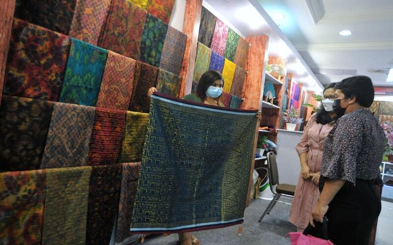 Pedagang melayani pembeli kain tenun Endek Bali di Denpasar, Bali, Senin (22/2/2021). Penjualan kain tenun Endek meningkat hingga 70 persen menjelang pemberlakuan Surat Edaran Gubernur Bali No. 04 Tahun 2021 mulai Selasa (23/2) yang salah satunya berisi imbauan penggunaan busana berbahan kain tenun Endek Bali atau kain tenun tradisional Bali dalam berbagai aktivitas setiap hari Selasa. - Antara/Fikri Yusuf.