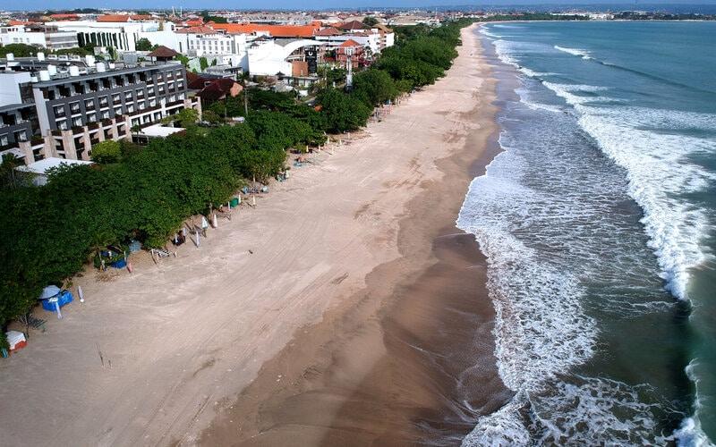 Suasana kawasan wisata Pantai Kuta yang ditutup sementara tampak lengang di Badung, Bali, Minggu (31/5/2020). Salah satu destinasi pariwisata utama di Pulau Dewata tersebut masih ditutup dari aktivitas masyarakat dan kunjungan wisatawan sebagai upaya pencegahan penyebaran Covid-19. - Antara/Fikri Yusuf.