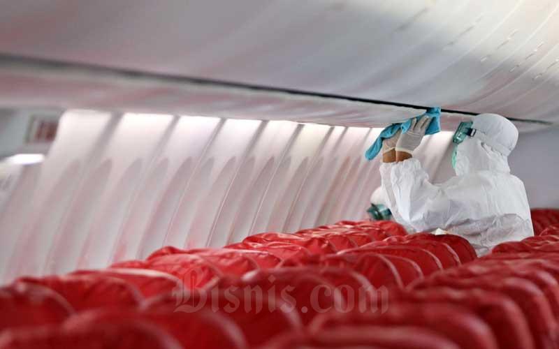 Petugas melakukan penyemprotan cairan disinfektan saat proses sterilisasi pada pesawat Lion Air Boeing 737-800 di Bandara Soekarno-Hatta, Tangerang, Banten, Selasa (17/3/2020). Bisnis - Eusebio Chrysnamurti\n