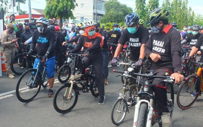 Gubernur Jawa Timur Khofifah Indar Parawansa bersepeda bersama para pejabat pemerintah sambil mengajak warga memakai masker  - Antara/Zumrotun Solichah