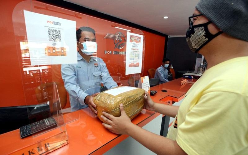 Petugas melayani pelanggan yang akan mengirim paket barang di Kantor Pos Sumedang, Kabupaten Sumedang, Jawa Barat, Kamis (25/2). - Bisnis/Rachman