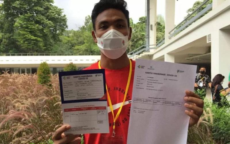 Sprinter Lalu Muhammad Zohri menunjukkan kartu vaksinasi Covid-19 seusai menerima suntikan pertama vaksin di Istora Gelora Bung Karno, Jakarta, Jumat (26/2/2021)./Antara - Shofi Ayudiana