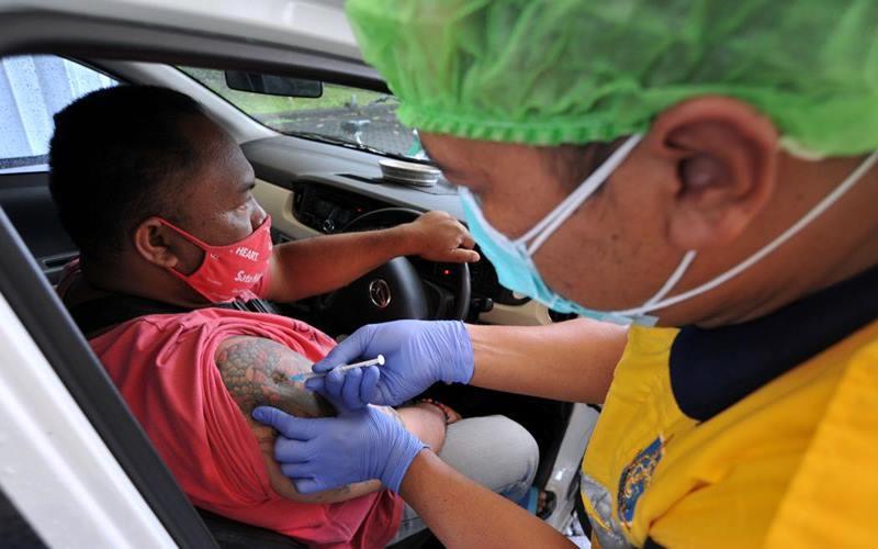 Vaksinator menyuntikkan vaksin Covid-19 kepada pekerja sektor pariwisata yang berada di atas kendaraan saat vaksinasi Covid-19 dengan sistem 'drive thru', di Nusa Dua, Badung, Bali, Minggu (28/2/2021) - Antara