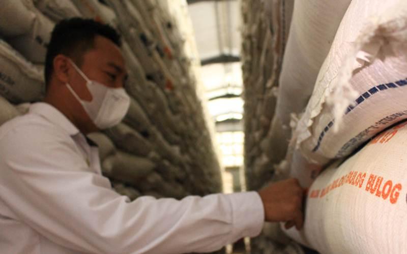 Ilustrasi - Seorang pegawai Perum Bulog Wilayah Sumatra Barat memperlihatkan stok beras yang tersedia di Gudang Ampalu Bypass Padang, yang diklaim cukup untuk memenuhi kebutuhan hingga momen Ramadhan 2021 nanti, Senin (1/3/2021). - Bisnis/Noli Hendra