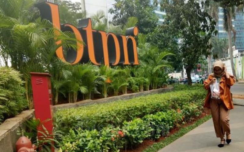 Pejalan kaki melintas di dekat logo PT Bank BTPN Tbk. di Jakarta, Selasa (16/10/2018). - JIBI/Dedi Gunawan