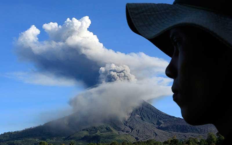 Pengendara melintas dengan latar belakang dengan latar belakang Gunung Sinabung yang menyemburkan material vulkanik di Desa Tiga Pancur, Karo, Sumatera Utara, Minggu (23/8/2020). Pusat Vulkanologi dan Mitigasi Bencana Geologi (PVMBG) menyatakan Gunung Sinabung berstatus level III atau siaga dan meminta masyarakat untuk tidak melakukan aktivitas di desa yang telah direlokasi. ANTARAFOTO - Edy Regar