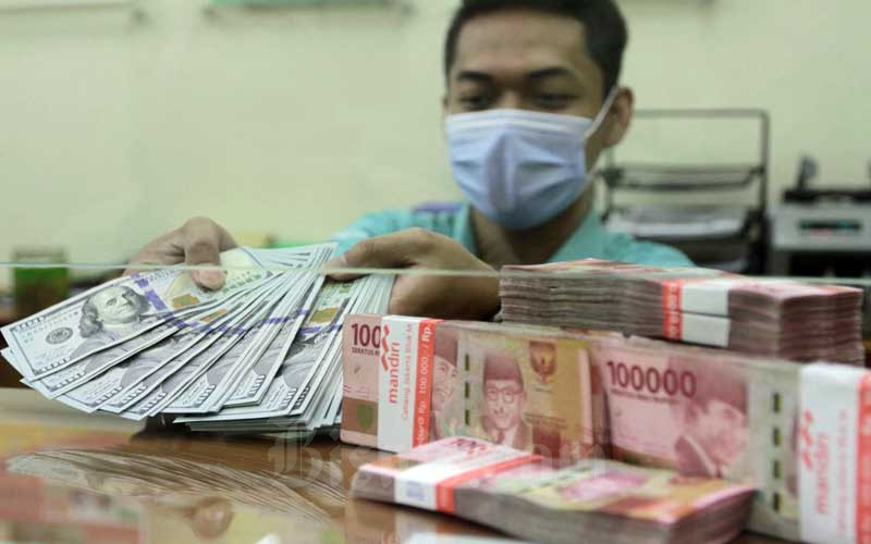 Pegawai menunjukan uang dolar dan rupiah di Jakarta, Senin (15/2/2021). Bisnis - Himawan L Nugraha
