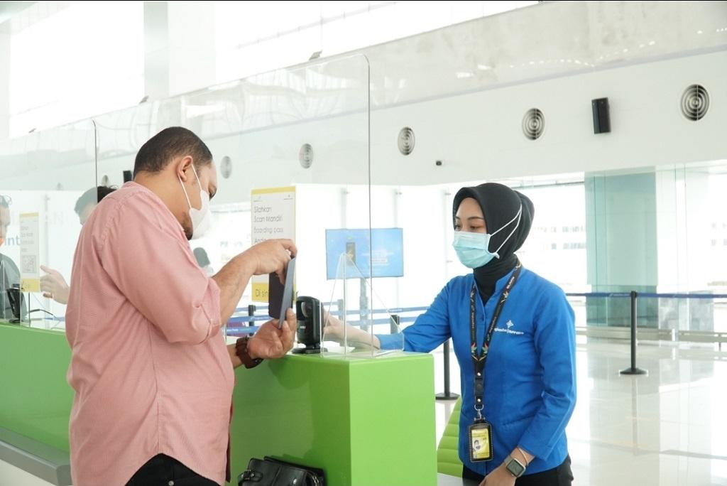 Foto: Petugas Bandara Jenderal Ahmad Yani Semarang mengarahkan calon penumpang pesawat udara untuk melakukan pemindaian mandiri boarding pass.