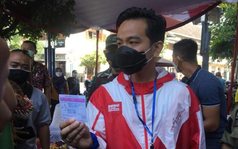 Wali Kota Solo Gibran Rakabuming Raka menunjukkan kartu vaksinasi Covid-19, Sabtu (27/2/2021). JIBI - Solopos.com/Farida Trisnaningtyas