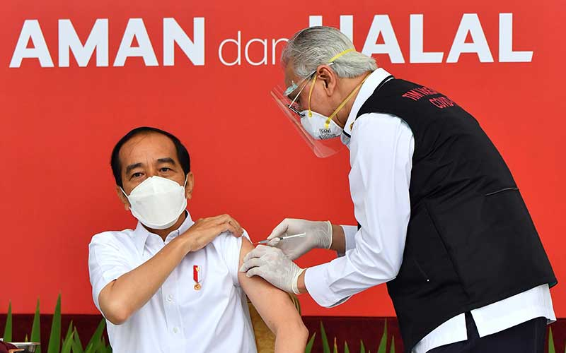 Presiden Joko Widodo bersiap disuntik dosis pertama vaksin Covid-19 produksi Sinovac oleh vaksinator Wakil Ketua Dokter Kepresidenan Abdul Mutalib (kanan) di beranda Istana Merdeka, Jakarta, Rabu (13/1/2021). Penyuntikan perdana vaksin Covid-19 ke Presiden Joko Widodo tersebut menandai dimulainya program vaksinasi di Indonesia. ANTARA FOTO/HO - Setpres/Agus Suparto