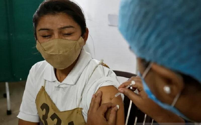 Seorang polisi wanita bereaksi saat menerima suntikan vaksin Covid-19, COVISHIELD yang diproduksi oleh Institut Serum India, di Rumah Sakit Umum di Ahmedabad, India, Minggu (31/1/2021). - Reuters/Antara\r\n