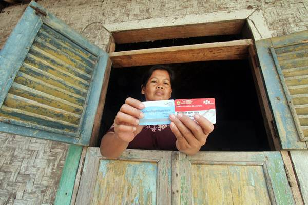 Warga menunjukan kartu peserta Program Keluarga Harapan (PKH) di Desa Gunung Sari, Citeureup, Bogor, Jawa Barat, Jumat (14/12/2018). - ANTARA/Yulius Satria Wijaya