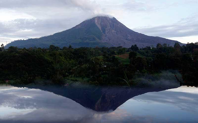 Refleksi Gunung Sinabung terihat dari Desa Tiga Pancur, Kabupaten Karo, Sumatera Utara, Kamis (19/11/2020). - Antara/Irwansyah Putra