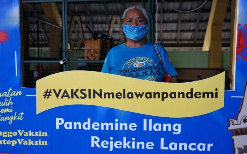 Peserta vaksinasi berpose usai divaksin saat vaksinasi Covid-19 massal di Pasar Beringharjo, Yogyakarta, Senin (1/3/2021). Vaksinasi Covid-19 massal kepada para pedagang kaki lima, pelaku usaha, penjaga toko hingga karyawan yang ada di Jalan Malioboro sampai ke Alun-alun Yogyakarta dengan jumlah sekitar 19.900 orang itu ditargetkan selesai dalam enam hari ke depan. - Antara/Andreas Fitri Atmoko.