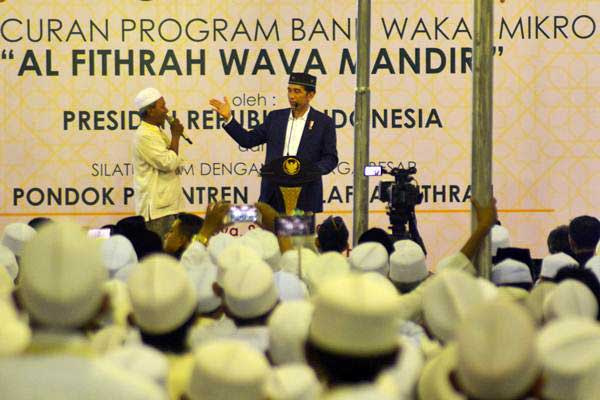 Presiden Joko Widodo (kanan) memberikan kuis kepada peserta dalam peresmian Bank Wakaf Mikro Al Fithrah Wava Mandiri di Pondok Pesantren As Salafi Al Fithrah, Surabaya, Jawa Timur, Jumat (9/3/2018). - Antara/Umarul Faruq