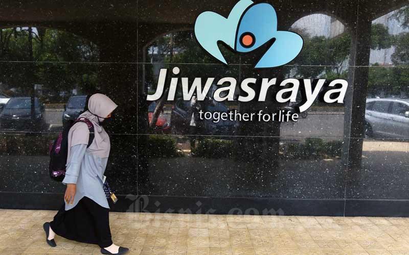 Warga melintasi logo Asuransi Jiwasraya di Jakarta, Senin (5/10/2020). Bisnis - Eusebio Chrysnamurti