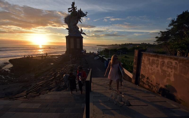 Wisatawan berjalan di dekat patung Gajah Mina saat mengunjungi Pantai Pererenan, Badung, Bali, Senin (1/3/2021). Badan Pusat Statistik (BPS) merilis jumlah kunjungan wisatawan mancanegara ke Indonesia pada bulan Januari 2021 mengalami penurunan sebesar 89,05 persen dibandingkan dengan bulan Januari 2020, yaitu dari 1,29 juta kunjungan menjadi 141,26 ribu kunjungan. - Antara/Nyoman Hendra Wibowo.