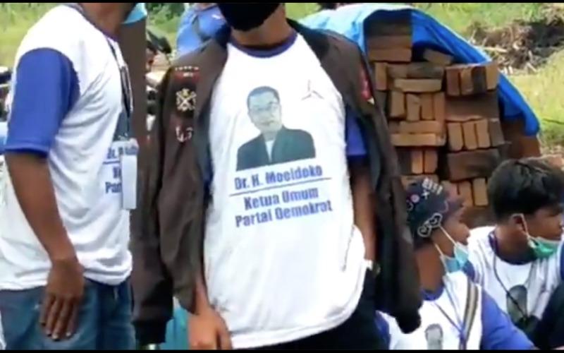 Tangkap layar video menunjukkan sekelompok orang tengah berjaga dengan pakaian seragam, kaos putih biru,  dengan cetakan foto diriKepala Staf Kepresidenan Moeldoko dan disertai tulisan,
