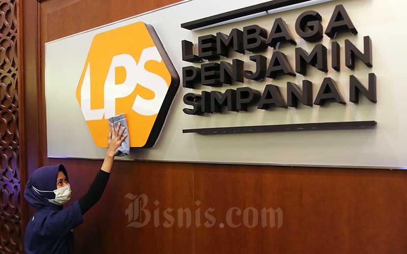 Karyawan membersihkan logo Lembaga Penjamin Simpanan (LPS) di Jakarta, Jumat (10/7/2020). Bisnis - Eusebio Chrysnamurti