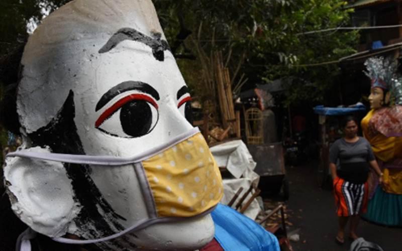 Ondel-ondel dipasangi masker di kawasan Kramat Pulo, Jakarta, Kamis (13/8/2020). - Antara/Indrianto Eko Suwarso
