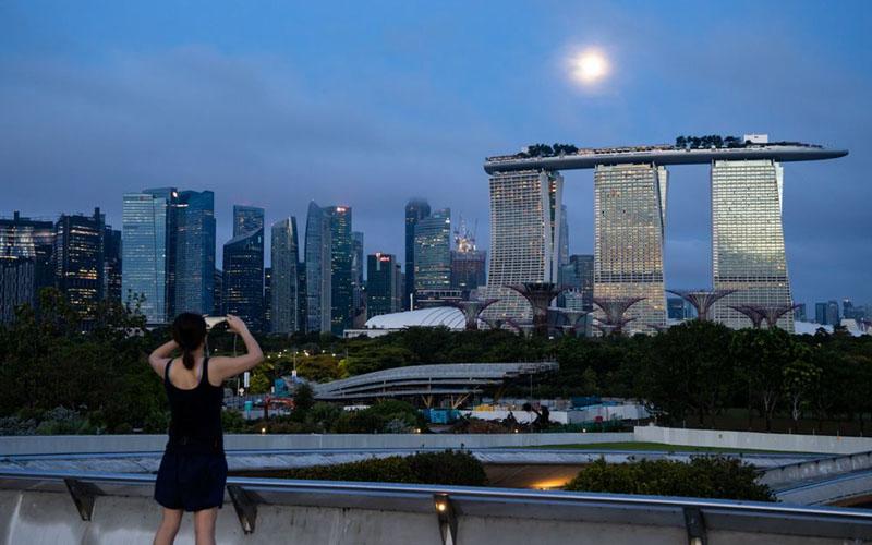 Seseorang mengambil gambar Marina Bay Sands Hotel & Casino Singapura./Bloomberg - SeongJoon Cho