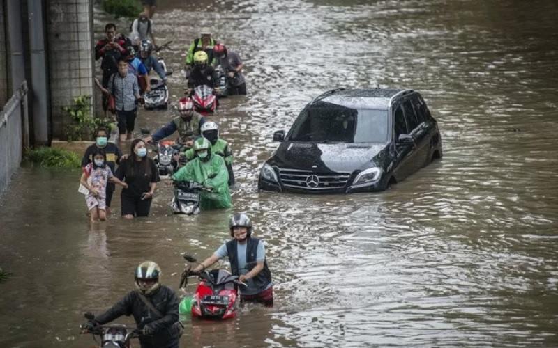 Warga mendorong sepeda motornya melintasi banjir di Jalan Kapten Tendean, Mampang Prapatan, Jakarta, Sabtu (20/2/2021). - Antara\r\n