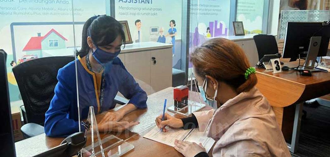 Karyawan melanyani nasabah di kantor Allianz di Jakarta, Senin (1/2/2021). Bisnis - Abdurachman