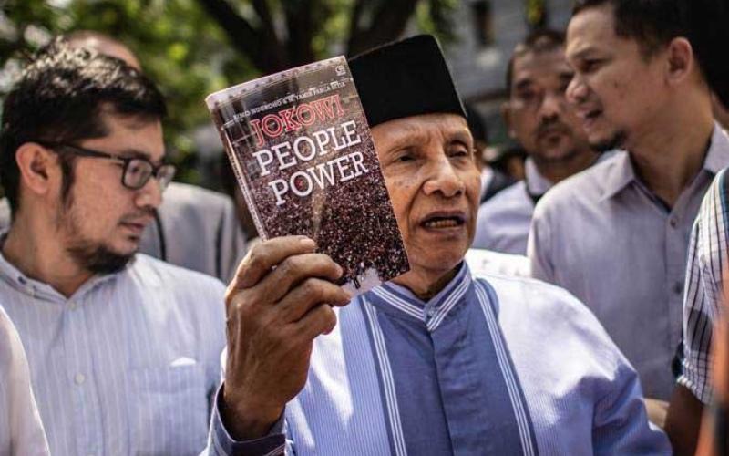 Amien Rais (tengah) menunjukkan buku berjudul Jokowi People Power saat jeda pemeriksaan untuk salat Jumat di Direktorat Reserse Kriminal Umum (Ditreskrimum) Polda Metro Jaya, Jakarta, Jumat (24/5/2019). - ANTARA FOTO/Aprillio Akbar