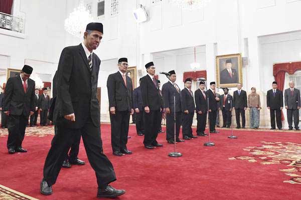 Kepala Badan Pelaksana Badan Pengelola Keuangan Haji (BPKH) Anggito Abimanyu (kedua kiri) bersiap menandatangani berita acara pelantikan Dewan Pengawas dan Badan Pelaksana BPKH oleh Presiden Joko Widodo di Istana Negara, Jakarta, Rabu (26/7). - ANTARA/Puspa Perwitasari
