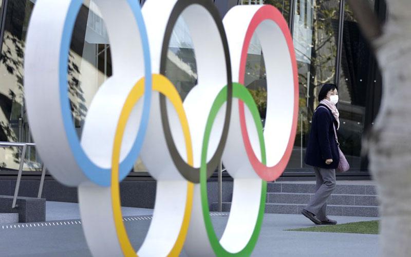 Seorang pejalan kaki yang mengenakan masker berjalan melewati cincin Olimpiade di luar Museum Olimpiade Jepang dekat Stadion Nasional Baru, di Tokyo./Bloomberg - Kiyoshi Ota