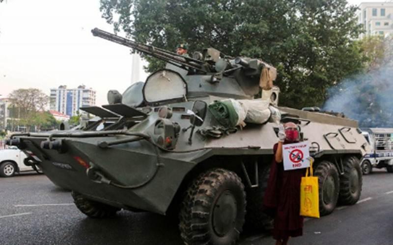 Seorang biksu Buddha memegang tanda berdiri di samping kendaraan lapis baja saat protes terhadap kudeta militer, di Yangon, Myanmar, Minggu (14/2/2021). - Antara/Reuters/Stringer
