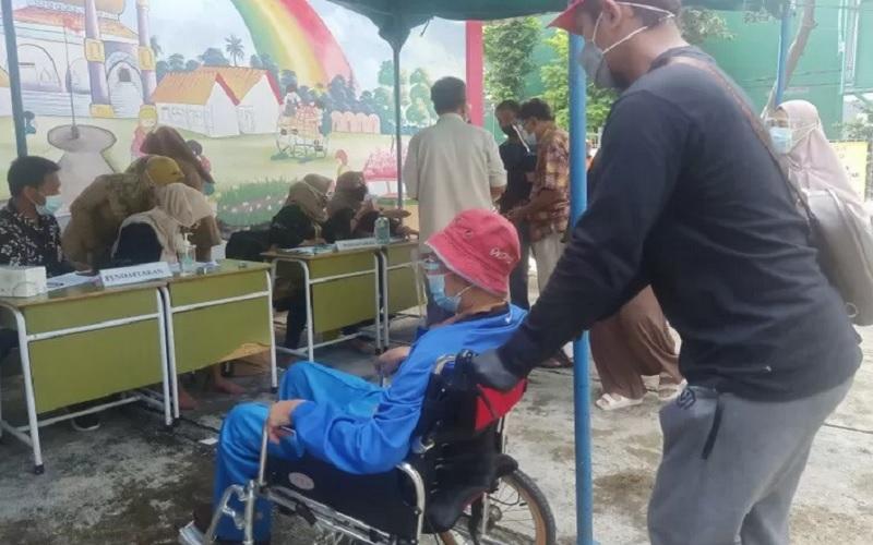 Masyarakat penerima manfaat Vaksin Covid-19 dari kelompok manula mendatangi meja registrasi di Sekolah TK Al Muhazirin, Pondok Kopi, Jakarta Timur, menggunakan kursi roda, Senin (8/3/2021). - Antara