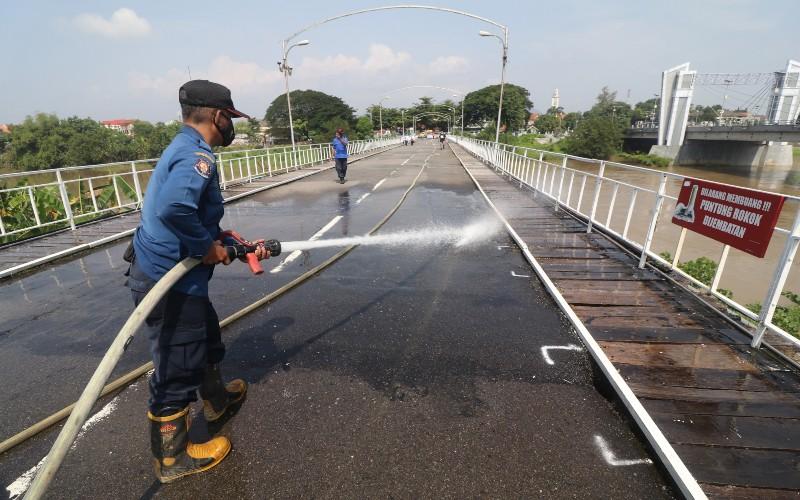 Petugas pemadam kebakaran menyemprotkan air untuk membersihkan Jembatan Lama Kediri (Brug Over Den Brantas de Kediri) di Kota Kediri, Jawa Timur, Kamis (18/3/2021). Jembatan Lama Kediri berusia 152 tahun tersebut merupakan jembatan cagar budaya berkonstruksi besi pertama di Pulau Jawa yang rutin mendapatkan perawatan untuk menjaga eksistesinya. - ANTARA FOTO/Prasetia Fauzani