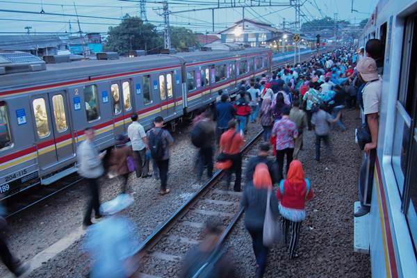 Penumpang KRL Commuterline berjalan melewati rel antara stasiun Manggarai-Jatinegara, karena KRL yang mereka naiki tidak bisa jalan akibat listrik saluran atas KRL mengalami gangguan di stasiun Jatinegara, Jakarta, Selasa (27/10). - Antara